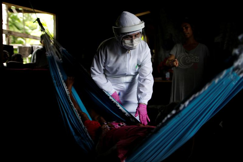 "Maria de Nazare 80, lies on a hammock as she is checked by Marilia Correa, 38, a nurse, at her home at the riverside community Pinheiro, as healthcare workers visit riverside communities to check on residents during the coronavirus disease (COVID-19) outbreak, in the municipality of Portel, at Marajo island, Para state, Brazil, June 6, 2020. REUTERS/Ueslei Marcelino SEARCH ""COVID-19 BRAZIL AMAZON"" FOR THIS STORY. SEARCH ""WIDER IMAGE"" FOR ALL STORIES TPX IMAGE OF THE DAY"