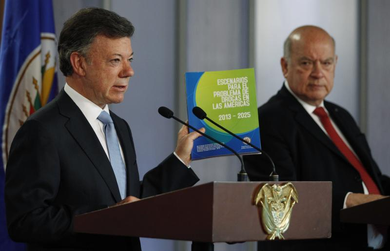 Colombia's President Juan Manuel Santos, left, holds a copy of a regional study the illicit drug trade presented by OAS chief Jose Miguel Insulza, right, during a joint press conference at the Presidential Palace in Bogota, Colombia, Friday, May 17, 2013. The $2.2 million study which emphasizes drug abuse as primarily a public health issue, makes no firm recommendations, instead suggesting several possible ways to stem the illicit drug trade, which has fueled violent crime and corruption and even destabilized governments. (AP Photo/Fernando Vergara)
