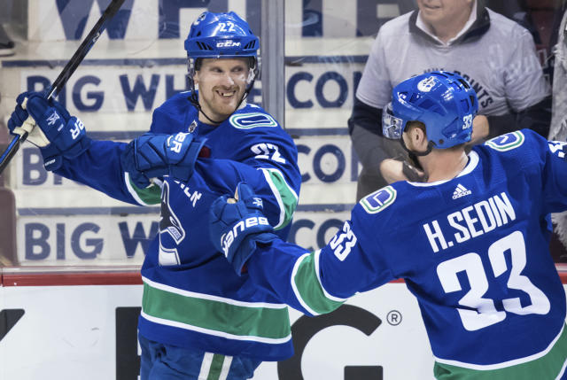 Vancouver Canucks' Daniel Sedin, left, celebrates his goal with his twin brother, Henrik Sedin, both of Sweden, against the Arizona Coyotes during the second period of an NHL hockey game Thursday, April 5, 2018, in Vancouver, British Columbia. (Darryl Dyck//The Canadian Press via AP)