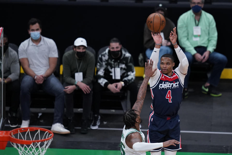 Fans wearing protective masks watch as Washington Wizards guard Russell Westbrook (4) takes a shot during the first half of an NBA basketball Eastern Conference Play-in game, Tuesday, May 18, 2021, in Boston. (AP Photo/Charles Krupa)