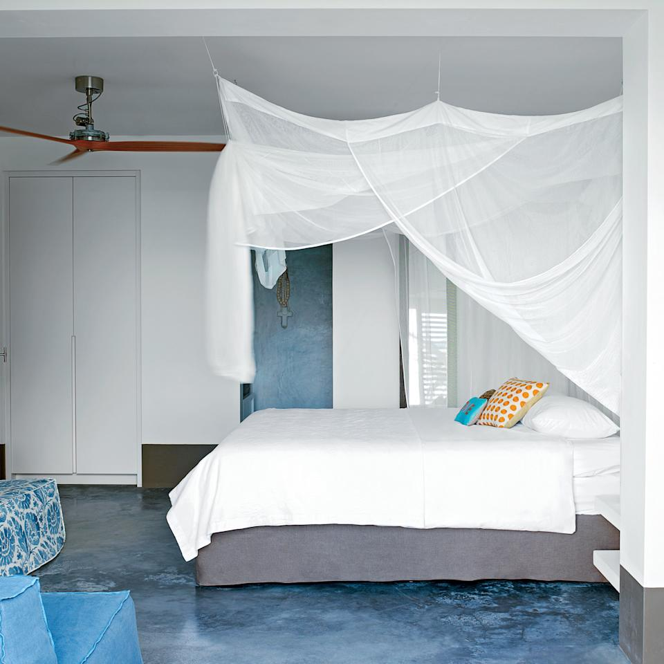 <p>Designer Piet Boon and business partner Karin Meyn designated this Caribbean home's lower level for bedrooms and baths, where gauzy canopies and white linens soften the concrete surroundings.</p>
