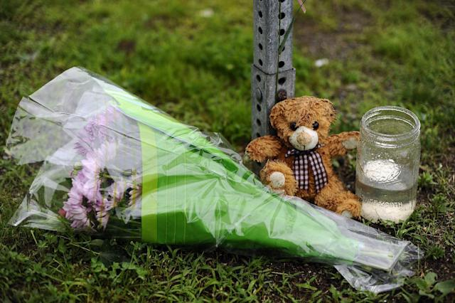 A teddy bear, flowers and a candle are the only items left at the entrance to Sandy Hook Elementary School on the six-month anniversary of the Dec. 14 shooting in Newtown, Conn., Friday, June 14, 2013. Newtown held a moment of silence Friday for the victims of the massacre at Sandy Hook Elementary School at a remembrance event that doubled as a call to action on gun control, with the reading of names of thousands of victims of gun violence. (AP Photo/Jessica Hill)