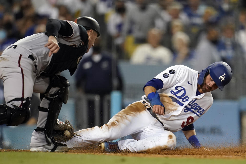 Los Angeles Dodgers' Gavin Lux, right, is tagged out at home plate by Arizona Diamondbacks catcher Carson Kelly after a sacrifice fly by Mookie Betts during the fourth inning of a baseball game Monday, Sept. 13, 2021, in Los Angeles. (AP Photo/Marcio Jose Sanchez)