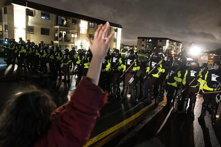 A person raises their hand facing a line of police