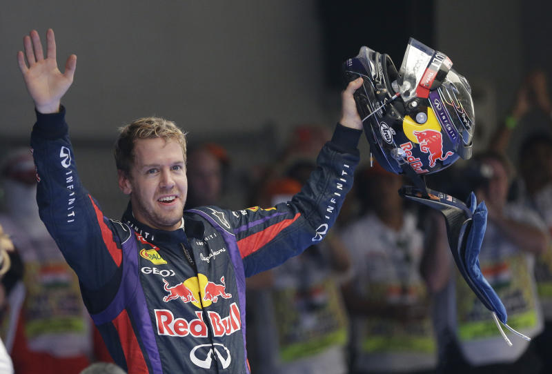 Red Bull driver Sebastian Vettel of Germany waves to the crowd after winning the Indian Formula One Grand Prix and his 4th straight F1 world drivers championship at the Buddh International Circuit in Noida, India, Sunday, Oct. 27, 2013. (AP Photo/Mark Baker)
