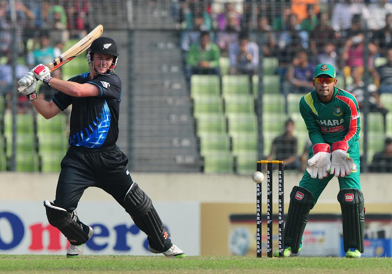 New Zealand batsman Colin Munro (L) plays a shot as the Bangladesh captain Mushfiqur Rahim looks on during the T20 match between Bangladesh and Zew Zealand at the Sher-e-Bangla National Cricket Stadium in Dhaka on November 6, 2013. AFP PHOTO/ Munir uz ZAMAN        (Photo credit should read MUNIR UZ ZAMAN/AFP/Getty Images)