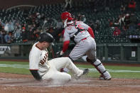 San Francisco Giants' Buster Posey, left, slides home to score past Cincinnati Reds catcher Tucker Barnhart during the sixth inning of a baseball game in San Francisco, Tuesday, April 13, 2021. (AP Photo/Jeff Chiu)