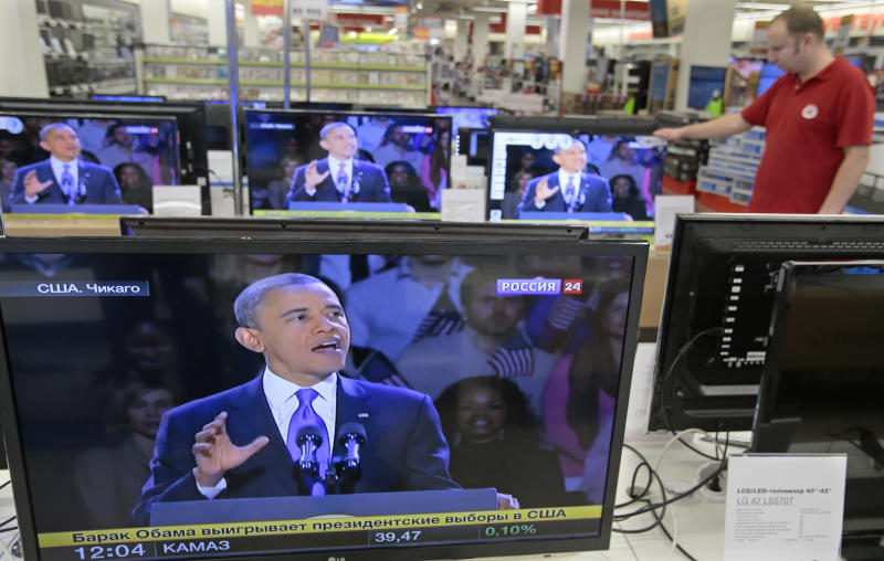 A shop assistant watches US President Barack Obama speaking on TV screen in Moscow TV shop, Russia, Wednesday, Nov. 7, 2012. Obama defeated Republican challenger former Massachusetts Gov. Mitt Romney. (AP Photo/Mikhail Metzel)
