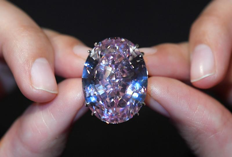 """A model poses with a 59.60-carat mixed cut diamond known as """"The Pink Star"""" with a sale estimate of US$ 60 million (GBP £48.4 million), at Sotheby's in London, Britain"""