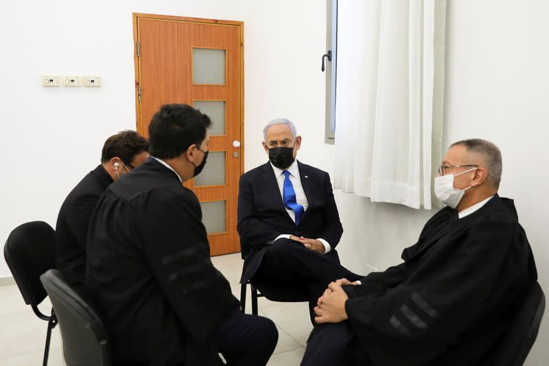 Israeli Prime Minister Benjamin Netanyahu, wearing a face mask, sits with his lawyers as his corruption trial resumes, at Jerusalem's District Court
