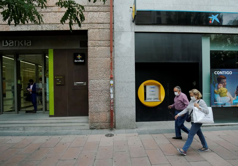 People walk past branches of Bankia and Caixabank in Madrid