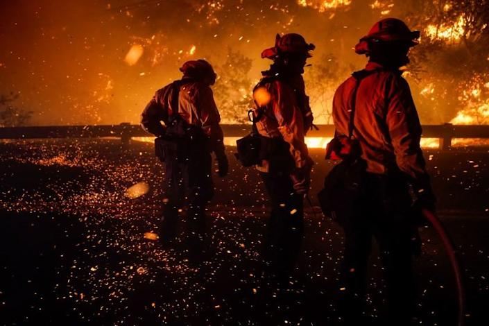 SILVERADO, CA - DECEMBER 03: Firefighters turn to shield themselves from the ember wash as they battle the Bond Fire, started by a structure fire that extended into nearby vegetation, along Silverado Canyon Road on Thursday, Dec. 3, 2020 in Silverado, CA. Dangerous fire weather conditions are in effect across wide swaths of Southern California as dry, gusty Santa Ana winds are expected from the northeast. (Kent Nishimura / Los Angeles Times)