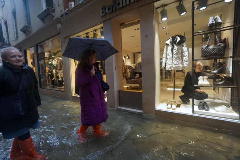 A shop assistant adjusts shoes as women outside wade through a flooded street on the occasion of a high tide, in Venice, Italy, Tuesday, Nov. 12, 2019. (Photo: Andrea Merola/ANSA via AP)