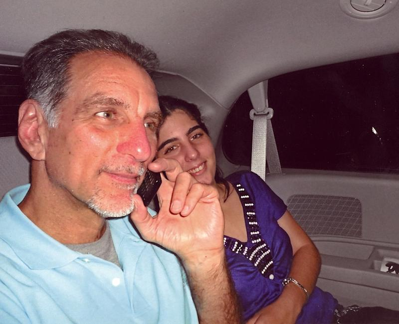 "FILE - In this file photo released on Wednesday Oct. 12, 2011 by the state media Cubadebate website, convicted Cuban agent Rene Gonzalez talks on the phone accompanied by his youngest daughter Ivette, after he was freed from a Florida jail, after serving 13 years of a 15-year sentence, in Marianna, Fla.  Gonzalez, one of the so-called ""Cuban Five,"" will be able to permanently remain in Cuba in exchange for renouncing his U.S. citizenship, a federal judge ruled Friday, May 3, 2013 after U.S. officials dropped their initial opposition. (AP Photo/Cubadebate, File)"