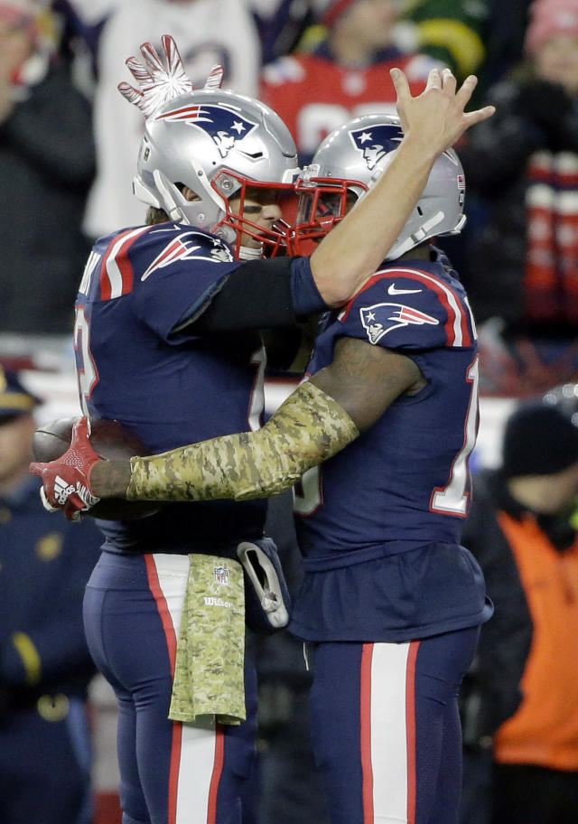 New England Patriots quarterback Tom Brady, left, celebrates his touchdown pass to wide receiver Josh Gordon, right, during the second half of an NFL football game against the Green Bay Packers, Sunday, Nov. 4, 2018, in Foxborough, Mass. (AP Photo/Steven Senne)