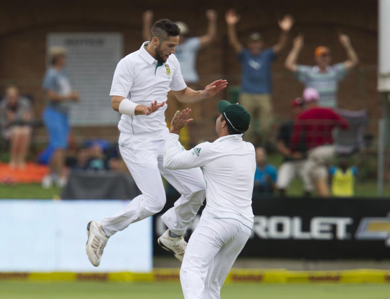 South Africa's Wayne Parnell (L) and Dean Elgar celebrate the wicket of Australia's Shaun Marsh (not in picture) during the second day of the second cricket test match in Port Elizabeth, February 21, 2014. REUTERS/Rogan Ward (SOUTH AFRICA - Tags: SPORT CRICKET)