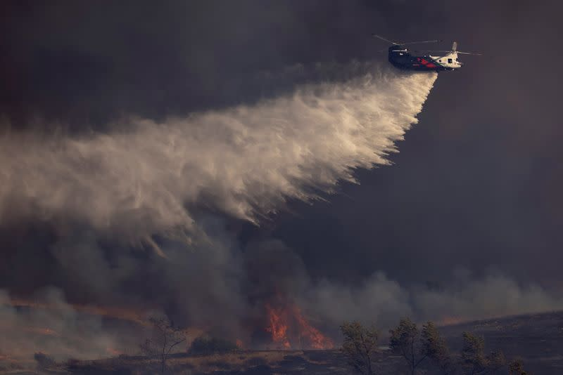 FILE PHOTO: A helicopter makes a water drop on flames as firefighters battle the wind driven Bond Fire wildfire near Lake Irvine in Orange County, California