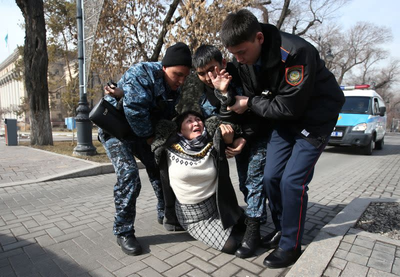 Kazakh law enforcement officers detain a woman during a rally held by opposition supporters in Almaty