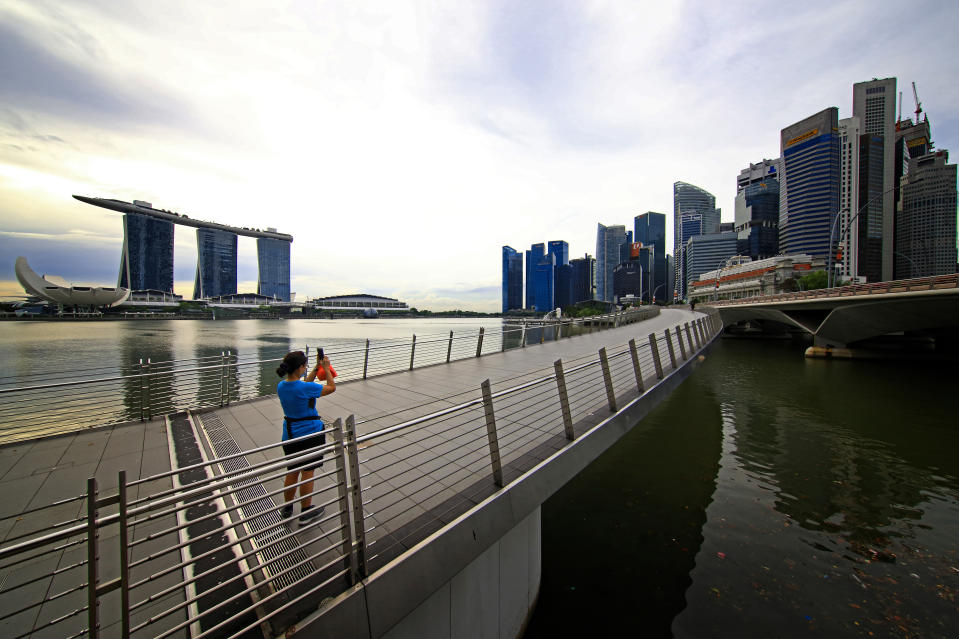 SINGAPORE - NOVEMBER 24: A woman wearing protective mask takes a photo of the city skyline at Marina Bay on November 24, 2020 in Singapore. As of November 23, the Ministry of Health confirmed five new imported COVID-19 cases bringing the country's total to 58,165. For the 13th straight day, there are no new cases of locally transmitted infection. (Photo by Suhaimi Abdullah/Getty Images)