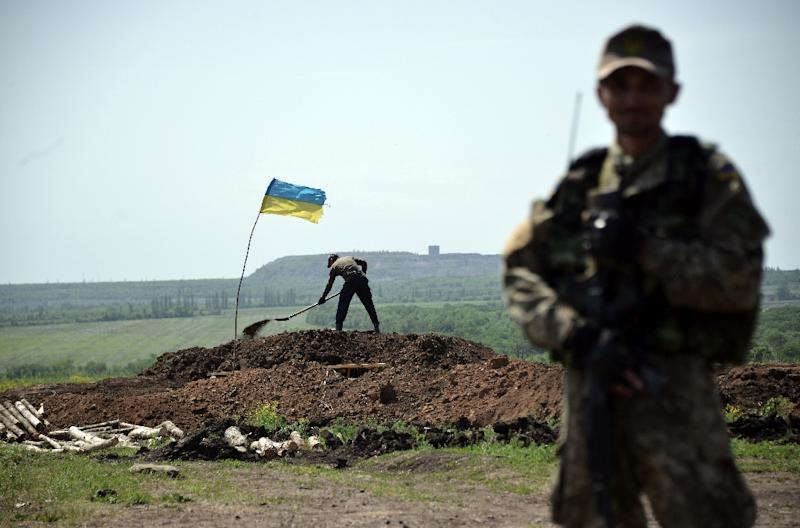 A Ukrainian serviceman stands as workers dig trenches on the frontline of fighting against pro-Russian separatist in eastern Ukraine on May 26, 2015