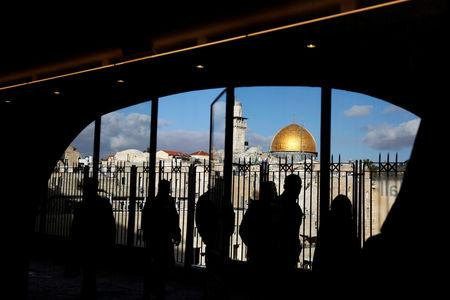 People look out from a building facing the Dome of the Rock (R), located in Jerusalem's Old City on the compound known to Muslims as Noble Sanctuary and to Jews as Temple Mount December 7, 2017. REUTERS/Ronen Zvulun