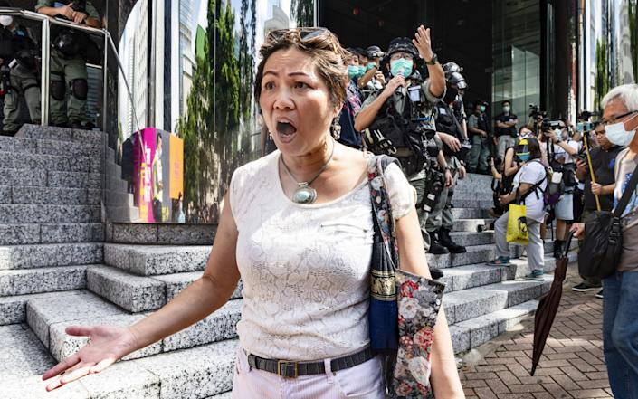 A woman argues with police officers during a march to celebrate US Independence Day outside the US consulate in Hong Kong - Anadolu Agency/Anadolu