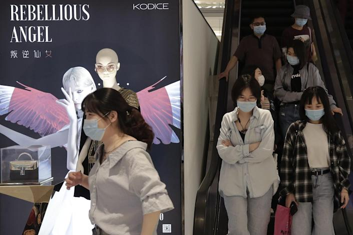 People wearing protective face masks ride an escalator.