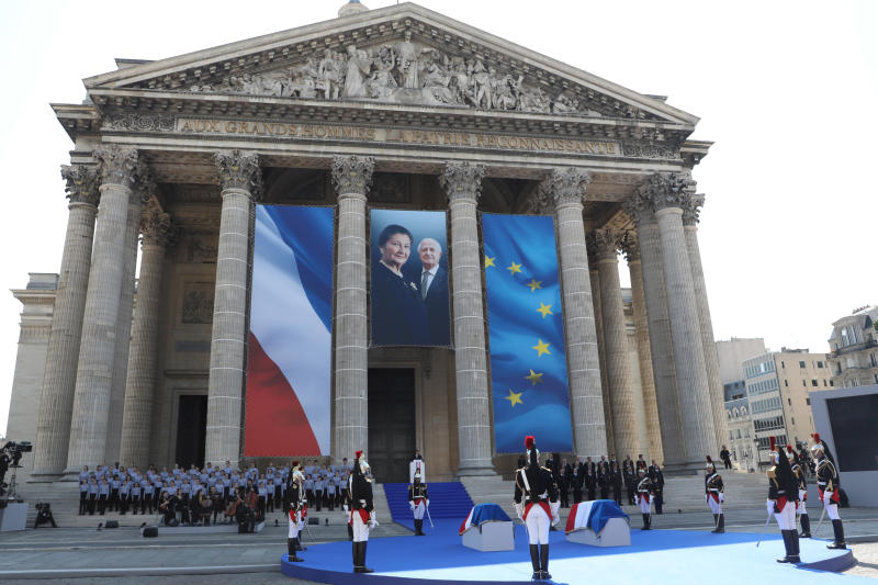 French President Emmanuel Macron, rear, delivers a speech in tribute to late Holocaust survivor Simone Veil and her late husband Antoine Veil during a national tribute before being laid to rest in the crypt of the Pantheon mausoleum, in Paris, France, Sunday, July 1, 2018. Simone Veil, who became one of France's most revered politicians, is getting the rare honor of being buried with her husband Antoine, who died in 2013, at the Pantheon, where French heroes are interred, one year after her death. (Ludovic Marin/Pool Photo via AP).