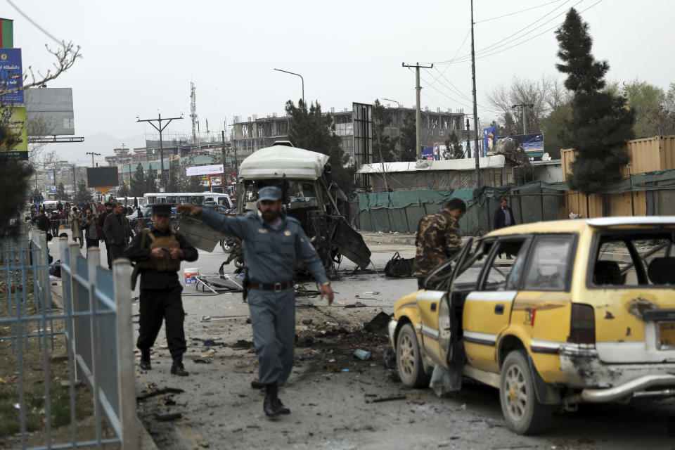 Security personnel inspect the site of a bomb attack in Kabul, Afghanistan, Monday, March 15, 2021. A bomb targeting a minibus in Afghanistan's capital exploded Monday wounding at least 15 civilians, police said, amid a surge in attacks in Kabul. (AP Photo/Rahmat Gul)