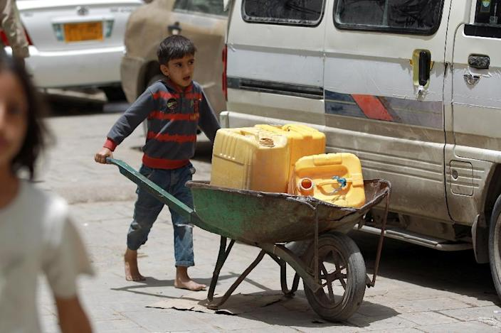 A Yemeni boy carries water containers in the old city of the capital Sanaa on April 7, 2015 (AFP Photo/Mohammed Huwais)
