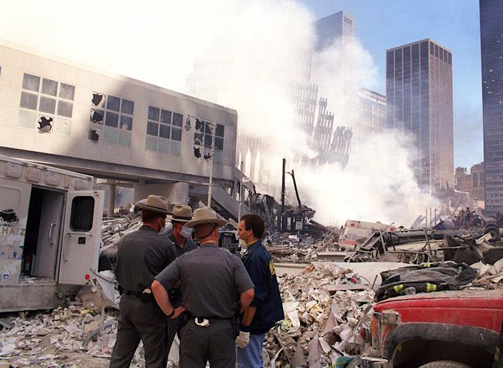<p>State police join rescue workers amid the rubble of the World Trade Center, Sept. 12, 2001, in New York. Remains of the facade of the World Trade Center are seen through the smoke in the background. (Photo: Virgil Case/AP) </p>