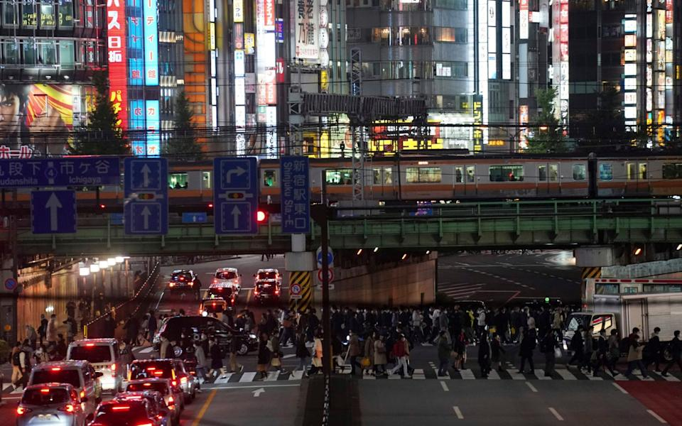 Pedestrians using a crossing in Tokyo, which confirmed more than 400 new coronavirus cases today. - Eugene Hoshiko/AP