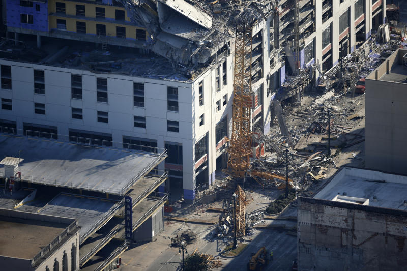 One of two large cranes from the Hard Rock Hotel construction collapse is seen on Rampart Street, in this aerial photo after they cranes were detonated for implosion in New Orleans, Sunday, Oct. 20, 2019. The Saenger Theater, seen in top of frame, appears undamaged from the operation. (AP Photo/Gerald Herbert)