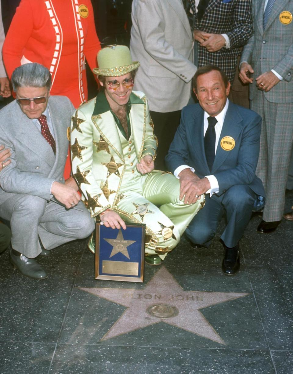 <p>Elton John receives a star on the Hollywood Walk of Fame on October 23, 1975, so of course he dresses head to toe in stars. (Photo: Getty Images) </p>