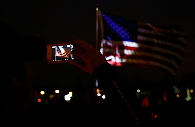 BOSTON, MA - APRIL 16: A person photographs the American flag with their cell phone during a vigil for eight-year-old Martin Richard, from Dorchester, who was killed by an explosion near the finish line of the Boston Marathon on April 16, 2013 at Garvey Park in Boston, Massachusetts. The twin bombings resulted in the deaths of three people and hospitalized at least 128. The bombings at the 116-year-old Boston race resulted in heightened security across the nation with cancellations of many professional sporting events as authorities search for a motive to the violence. (Photo by Jared Wickerham/Getty Images)