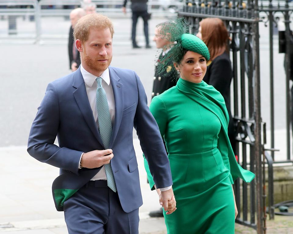 Prince Harry, Duke of Sussex in a suit and Meghan, Duchess of Sussex in a green dress and hat