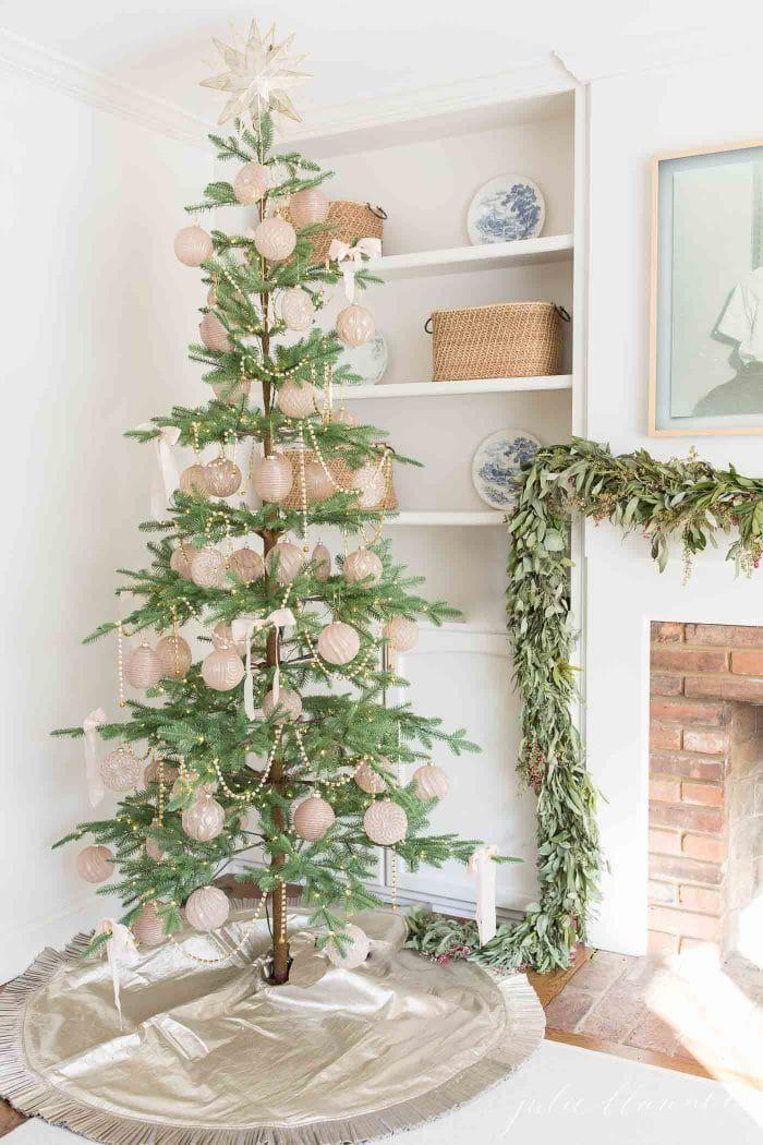 """<p>The perk of buying a skinny tree? You get a clear view of all of the ornaments and beaded garland.</p><p><em><a href=""""https://julieblanner.com/skinny-christmas-tree/"""" rel=""""nofollow noopener"""" target=""""_blank"""" data-ylk=""""slk:Get the tutorial at Julie Blanner »"""" class=""""link rapid-noclick-resp"""">Get the tutorial at Julie Blanner » </a></em></p>"""