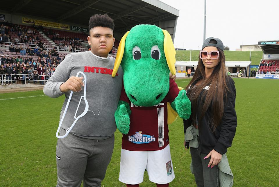 NORTHAMPTON, ENGLAND - APRIL 15:  Model Katy Price and her son Harvey pose with Northampton Town mascot Clarence the Dragon prior to a Celebrity Charity Match at Sixfields on April 15, 2018 in Northampton, England.  (Photo by Pete Norton/Getty Images)