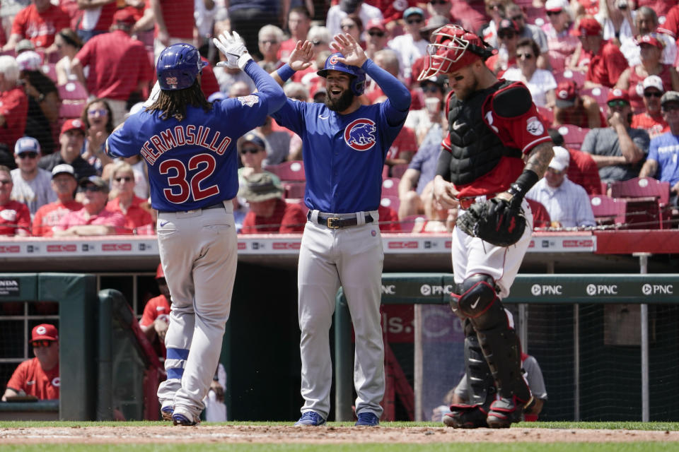 Cincinnati Reds catcher Tucker Barnhart (16) looks on as Chicago Cubs' Michael Hermosillo (32) celebrates with David Bote, center, after hitting a two run home run during the second inning of a baseball game in Cincinnati, Wednesday, Aug. 18, 2021. (AP Photo/Jeff Dean)