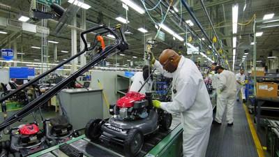 A Honda Power Equipment associate makes adjustments to a lawnmower in final assembly at the Swepsonville, NC plant