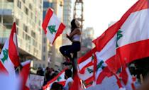 A demonstrator sits on a pole while carrying a national flag during an anti-government protest in downtown Beirut