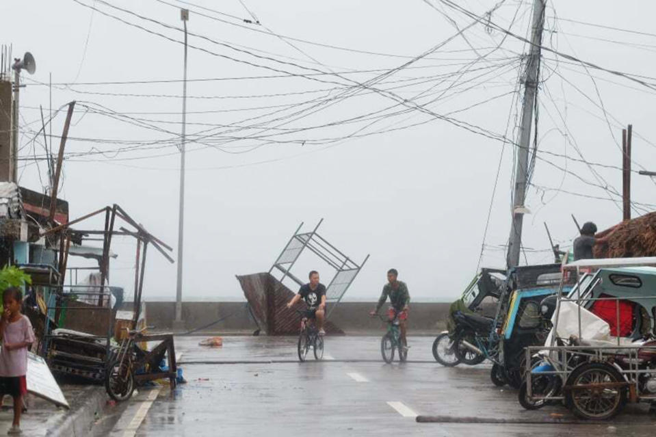 Residents walk past a toppled structure as waves batter the coast of Sorsogon province, central Philippines as Typhoon Goni hits the country on Sunday, Nov. 1, 2020. A super typhoon slammed into the eastern Philippines with ferocious winds early Sunday and about a million people have been evacuated in its projected path, including in the capital where the main international airport was ordered closed. (AP Photo)