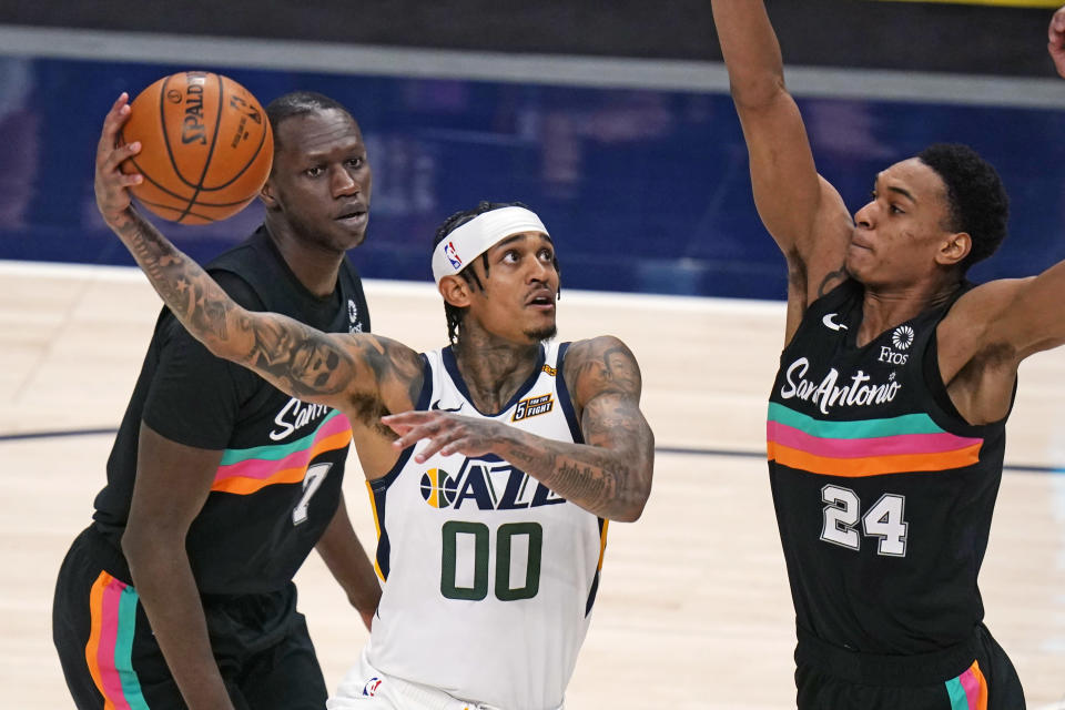 Utah Jazz guard Jordan Clarkson (00) goes to the basket as San Antonio Spurs guard Devin Vassell (24) defends during the second half of an NBA basketball game Wednesday, May 5, 2021, in Salt Lake City. (AP Photo/Rick Bowmer)