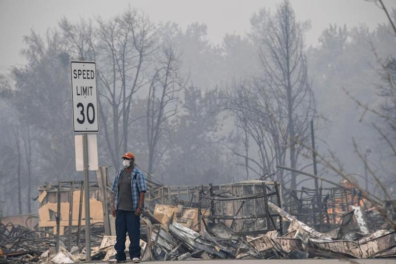 A man stands near some of the destruction caused by the Almeda Fire in Phoenix, Oregon, September 15, 2020.