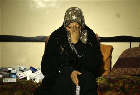 Suhad al-Katib, a Palestinian woman patient who suffers cancer reacts inside her house after she was not allowed to enter Israel, in Gaza City February 12, 2014. REUTERS/Mohammed Salem