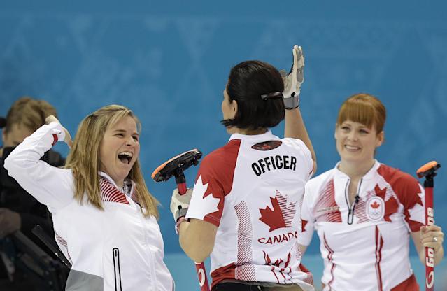 Canada's Jennifer Jones, left, celebrates with Jill Officer, center and Dawn McEwen, right, after beating Britain in the women's curling semifinal game at the 2014 Winter Olympics, Wednesday, Feb. 19, 2014, in Sochi, Russia. (AP Photo/Wong Maye-E)