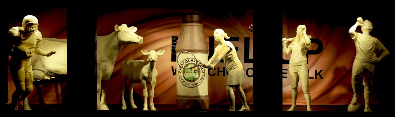 This undated photo, shows the traditional butter cow and calf that are now accompanied by four young student-athletes and a larger-than-life bottle of the official beverage that fuels them, chocolate milk. (American Dairy Association Mideast via AP)