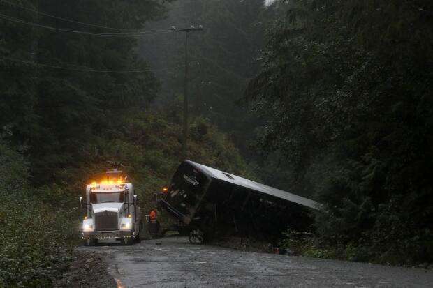 A tow-truck crew removes a bus from an embankment next to a logging road near Bamfield, B.C., on Sept. 14, 2019. Two students who died in the crash had not been wearing their seatbelts, according to the provincial coroner. (Chad Hipolito/Canadian Press - image credit)