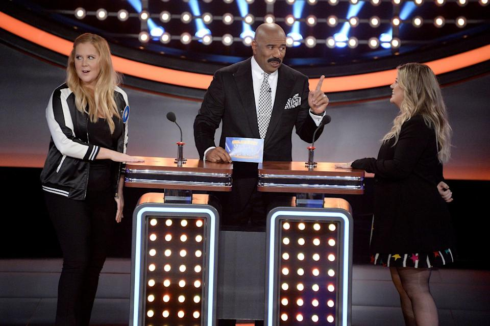"""Kelly Clarkson and Amy Schumer compete on """"Celebrity Family Feud,"""" hosted by Steve Harvey."""