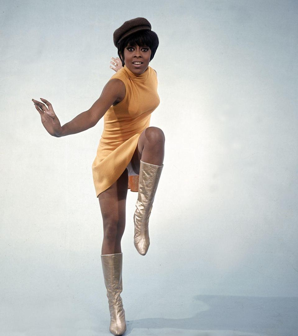 <p>Lola Falana stepping out in an orange minidress, tall gold boots and a pageboy hat.</p>